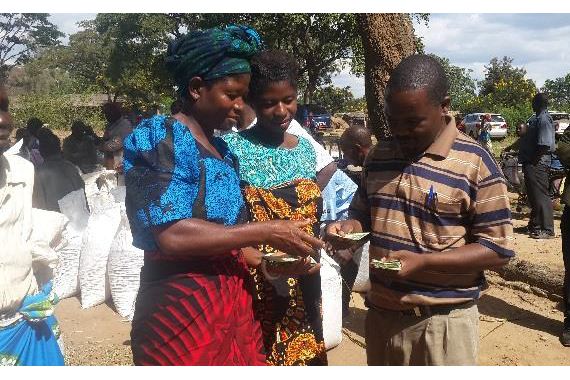 A small holder women farmer receiving payment from CPM-Agri Enterprises towards sale of seed under seed village model in Chadza